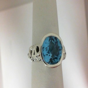 Sterling Silver Fashion Ring With One 10.00X8.00Mm Oval Blue Topaz And 2=0.05Tw Round Blue Sapphires Name: Dylani Collection- Blue Topaz Ring Size: 6.5